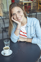 Young woman relaxing at cafe, portrait