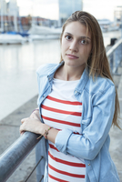 Young woman leaning against railing, portrait