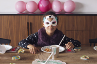 Girl wearing festive mask at birthday party