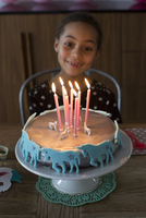 Girl preparing to blow out candles on birthday cake