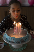 Girl blowing out candles on birthday cake