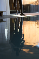 Man's reflection on spa swimming pool, low section