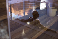 Man relaxing in swimming pool, reflected on glass door