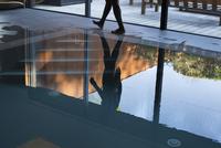 Man walking beside pool, reflected on water