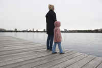 Mother and young daughter standing together on dock, looking at water