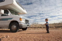 Toddler standing in front of motor home