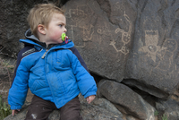 Toddler boy studying petroglyph in Yellowstone National Park, USA