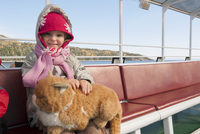 Little girl sitting on ferry boat with stuffed cat on her lap, portrait
