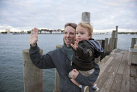 Mother and young son waving on pier