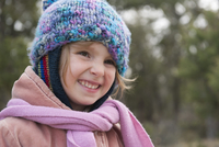 Little girl wearing knit hat and scarf, smiling, portrait