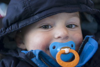 Toddler boy with pacifier in his mouth, portrait