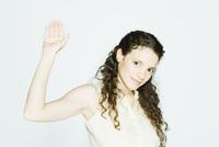 Young woman raising hand, portrait