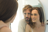 Couple looking in bathroom mirror together