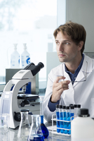 Scientist working in laboratory, looking away in thought