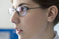 Young woman in glasses looking away in thought, profile