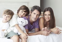 Parents and young sons relaxing together on bed, portrait