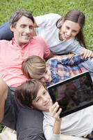 Boy photographing family with digital tablet camera