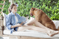 Young woman sitting beside dog outdoors, reading book