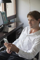 Businessman holding smartphone in office