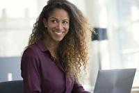 Woman using laptop computer, smiling