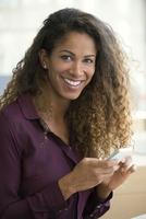 Woman using smartphone, smiling, portrait