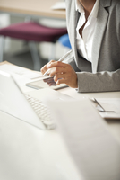 Businesswoman taking notes at meeting, cropped