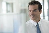 Businessman looking away, smiling, portrait
