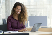 Businesswoman using laptop computer in office, smiling, portrait