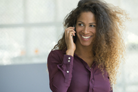 Woman talking on cell phone, smiling cheerfully