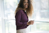Woman holding smartphone, smiling, portrait