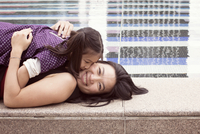 Mother and daughter lying together at edge of fountain, girl kissing woman's cheek