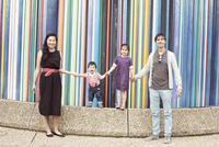 Family holding hands together in front of colorful striped sculpture, La Defense, Paris, France