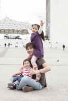 Father sitting on the ground with two children in city square