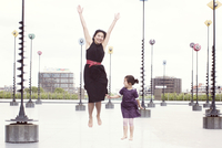 Mother and daughter jumping in front of whimiscal sculptures, La Defense, Paris, France