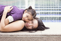 Mother and daughter lying together on edge of fountain, portrait