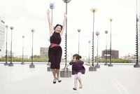 Mother and daughter jumping in front of whimiscal sculptures, La Defense, Paris, France 11001061870| 写真素材・ストックフォト・画像・イラスト素材|アマナイメージズ