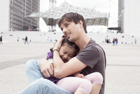 Father holding young daughter in his lap outdoors
