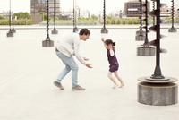 Father and daughter playing together in urban park