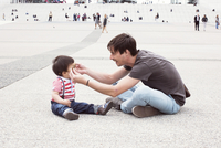 Father putting sunglasses on infant son outdoors