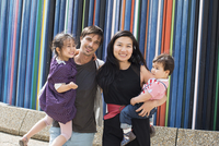 Family holding standing in front of colorful striped sculpture, La Defense, Paris, France