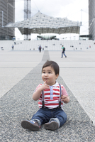 Baby boy sitting on the ground in city square