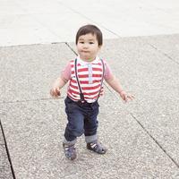 Baby boy walking on sidewalk with snack in hand