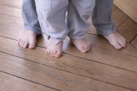 Close-up of child and baby's bare feet