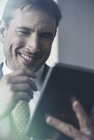 Businessman using digital tablet, smiling cheerfully
