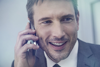 Businessman talking on cell phone, smiling cheerfully