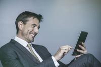 Man laughing while using digital tablet