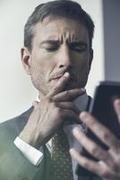 Businessman looking at digital tablet with furrowed brow