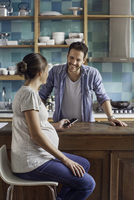 Pregnant wife chatting with husband in kitchen