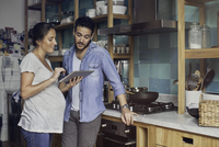Couple in kitchen looking at digital tablet together