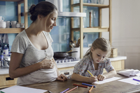 Pregnant mother watching daughter draw